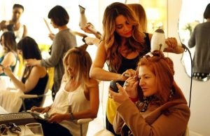 Gina Tennen, right, does her makeup as stylist Lorena Soria uses a blow dryer on her hair